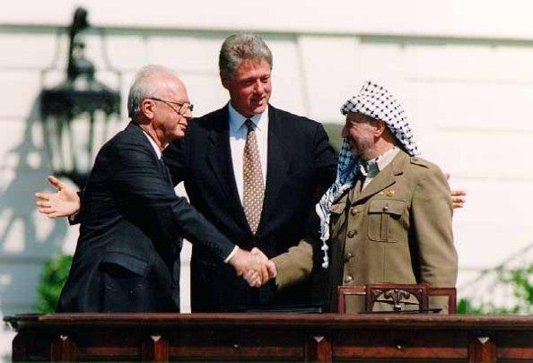 Yitzhak Rabin skakar hand med Yassir Arafat med Bill Clinton i bakgrunden, under ceremonin och signeringen av avtalet i Washington D.C., den 13 september 1993.